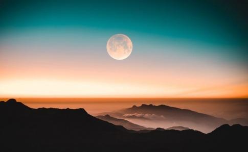 Ein Vollmond ist über Bergen im Sonnenaufgang oder Sonnenuntergang zu sehen