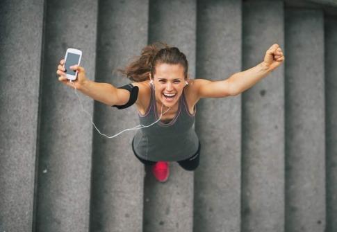 Eine Frau joggt durch den Park. Hinter ihr geht die Sonne auf. Sie wirkt glücklich und motiviert.