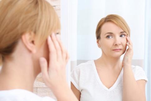 Eine Frau betrachtet im Spiegel ihre müden Augen