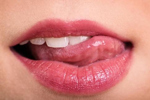 Mund einer Frau, die sich Lippen leckt.