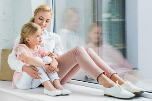 Eine Mutter sitzt entspannt mit dem Kind auf dem Bett