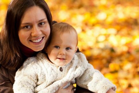Eine Mutter mit ihrem Baby im Arm im Herbst