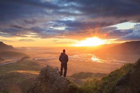 Ein Mann steht nachdenklich in den Bergen und fragt sich, wer bin ich
