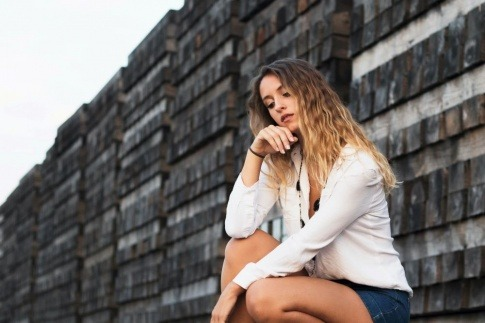 Eine Frau sitzt nachdenklich auf einer Bank