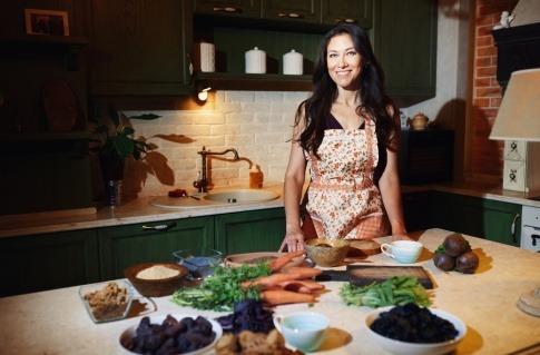 Nachhaltig zu kochen bedeutet, sich wie die Frau in diesem Bild an saisonalen und regionalen Lebensmitteln zu orientieren, die vor ihr auf dem Küchentresen liegen.