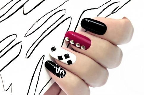 Eine Hand mit schwarzen, weißen und roten Fingernägel hält ein Blatt Papier