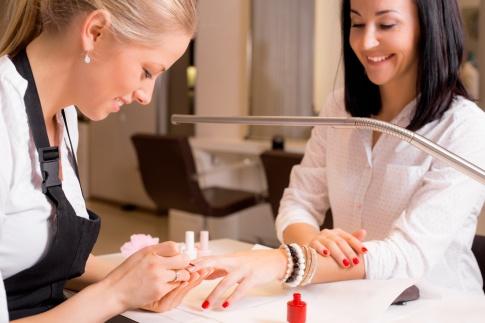 Eine Nageldesignerin kümmert sich um die Nägel ihrer Kundin