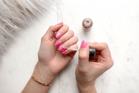 Eine Frau lackiert die Nägel in dünnen Schichten