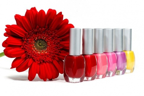Verschiedene Nagellacke stehen neben einer Blume