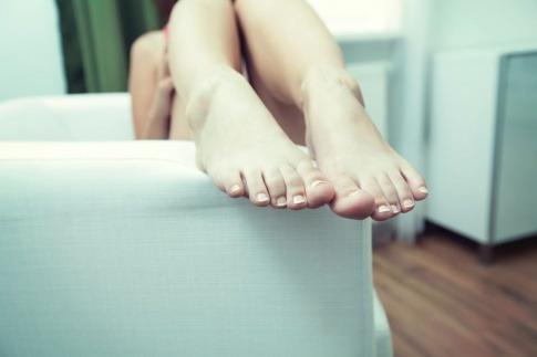 Eine Frau lässt ihre Beine aus der Badewange hängen und hat vielleicht Nagelpilz