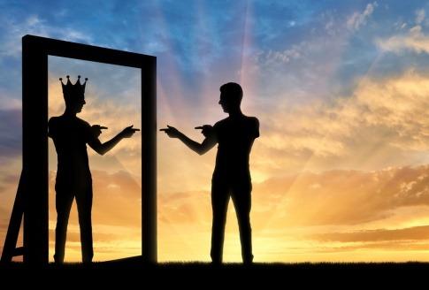 Die Silhouette eines Mannes, der sich selbst mit einer Krone auf seinem Kopf im Spiegelbild sieht und anfeuert - typisch für eine Narzissten Beziehung.