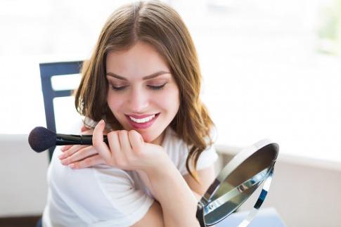 Frau mit Schminkpinsel und Spiegel