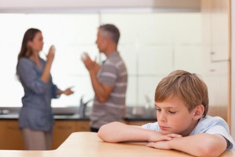 Eltern verbreiten in einer Küche negative Emotionen durch einen Streit, ein Junge sitzt im Vordergrund