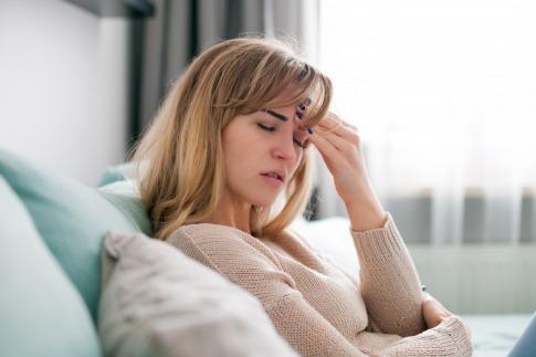 Eine Frau auf einem Sofa scheint negative Gefühle zu unterdrücken
