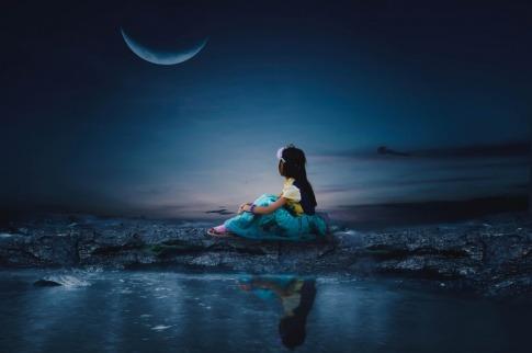 Eine Frau sitzt bei Neumond im September neben Wasser
