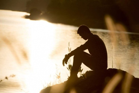 Ein Mann sitzt gedankenversunken und traurig auf einem Felsvorsprung und überlegt sich, wie man mit Niederlagen umgehen kann.