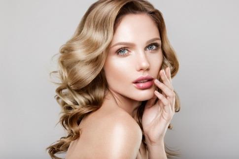 Eine Frau mit blonden langen Haaren und einem nudefarenen Make-up hält sich eine Hand ins Gesicht