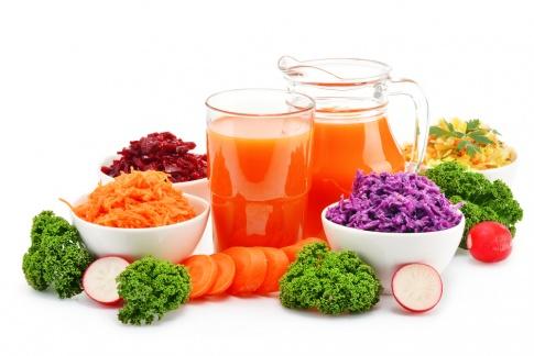 Obst und Gemüse, daneben ein Krug mit orangem Saft