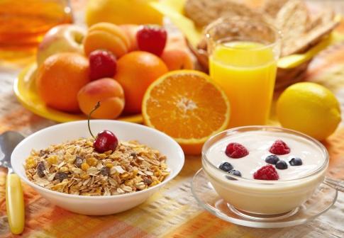 Im Vordergrund ist ein Müsli und eine Schüssel mit Joghurt abgebildet. Dahinter sind verschiedene Obstsorten, wie Orangen und Erdbeeren.