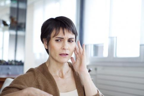 Eine Frau greift sich wegen Ohrgeräuschen ans Ohr