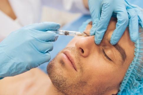 Mann während Botoxbehandlung im Gesicht