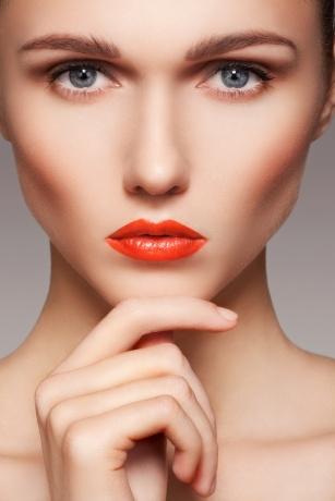 Eine Frau trägt ein natürliches Make up mit orangen Lippen