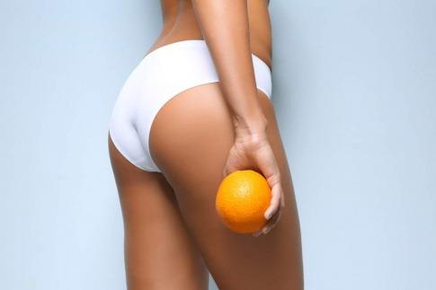 Oberschenkel einer Frau mit Orange in der Hand.