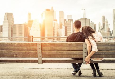 Ein Paar sitzt auf einer Bank vor einer Stadt