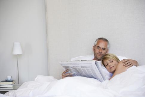Paar liegt im Bett, Mann liest Zeitung
