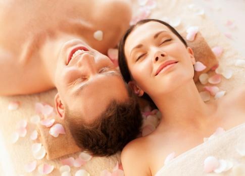 Ein Paar liegt Kopf an Kopf lächelnd und entspannt nebeneinander