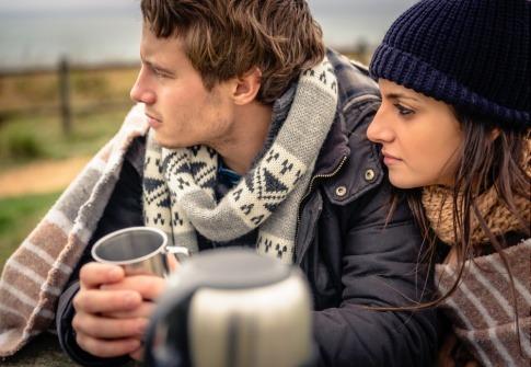 Ein Paar sitzt in einer kühlen Jahreszeit nebeneinander
