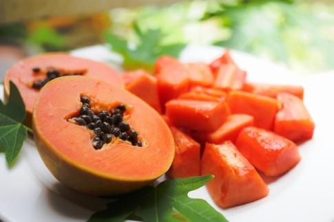 Das Bild zeigt eine ganze Papaya sowie eine in Stücke geschnittene Papaya vor einem neutralen Hintergrund.