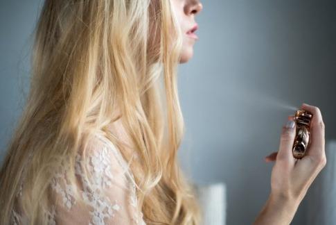 Eine Frau sprüht Parfum auf ihren Hals