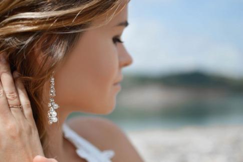 Eine Frau trägt Perlenschmuck, kombiniert mit glitzernden Steinen