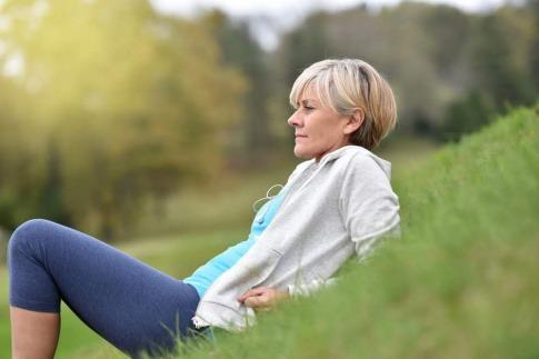 Eine Frau nutzt die Wechseljahre für die persönliche Entwicklung. Sie hat mit dem Joggen begonnen und ruht sich auf einer Wiese aus, während sie in die Ferne blickt.