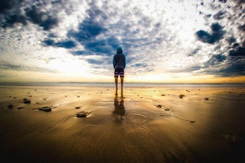 Eine Person steht am Strand unter einem dunklen Wolkenhimmel in einer besonderen Atmosphäre