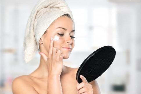 Frau mit schöner Haut schaut in den Spiegel