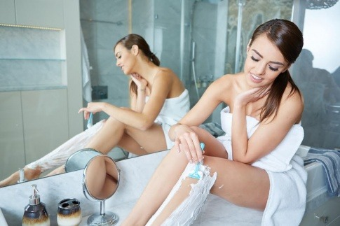 Eine Frau rasiert ihre Beine und vermeidet Pickel durch Rasiergel