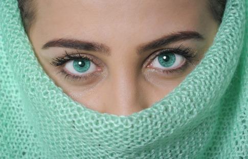Frau verdeckt ihr Gesicht mit Schal