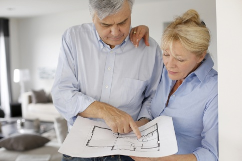Ein älteres Paar hat einen Plan in der Hand für altersgerechten Wohnhaus