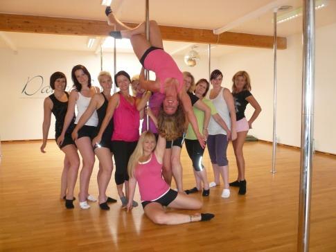 Eine Gruppe Damen steht vor Pole Dancestangen an einem Polterabend für Frauen