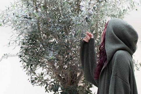 Eine Frau mit schöner Haut und schönen Haaren steht vor einem Olivenbaum mit Polyphenolen