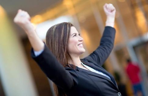 Eine Frau in einem Businessoutfit reckt triumphierend die Arme in die Luft und wirkt glücklich. Es scheint, als wüsste sie genau, wie sie ihr Potential entwickeln und nutzen kann.