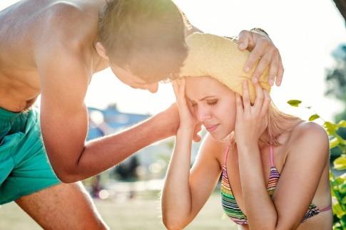 Junge Frau am Strand mit nassem Tuch auf der Stirn.