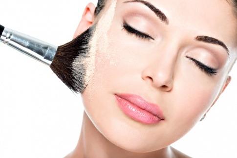 Eine Frau trägt Puder Make up mit einem Pinsel auf