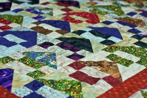 Quilten für Anfänger muss nicht schwierig sein. Das Bild zeigt eine farbenfrohe Patchwork Decke.