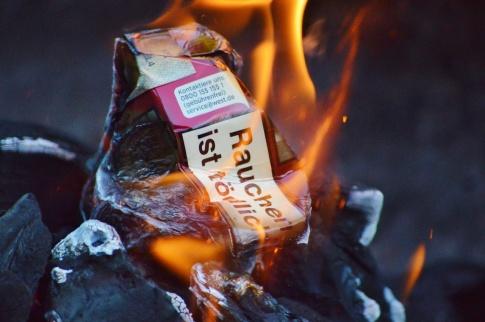 Eine Packung Zigaretten verbrennt im Feuer