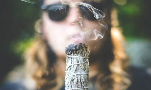 Mann hält ein rauchendes Salbeibündel