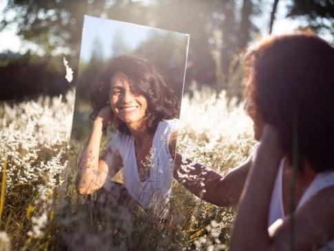 Eine Frau mit reifer Haut sitzt vor einem Spiegel