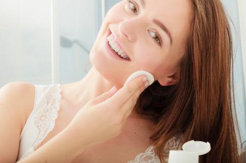 Eine Frau reinigt ihr Gesicht mit Mizellenwasser